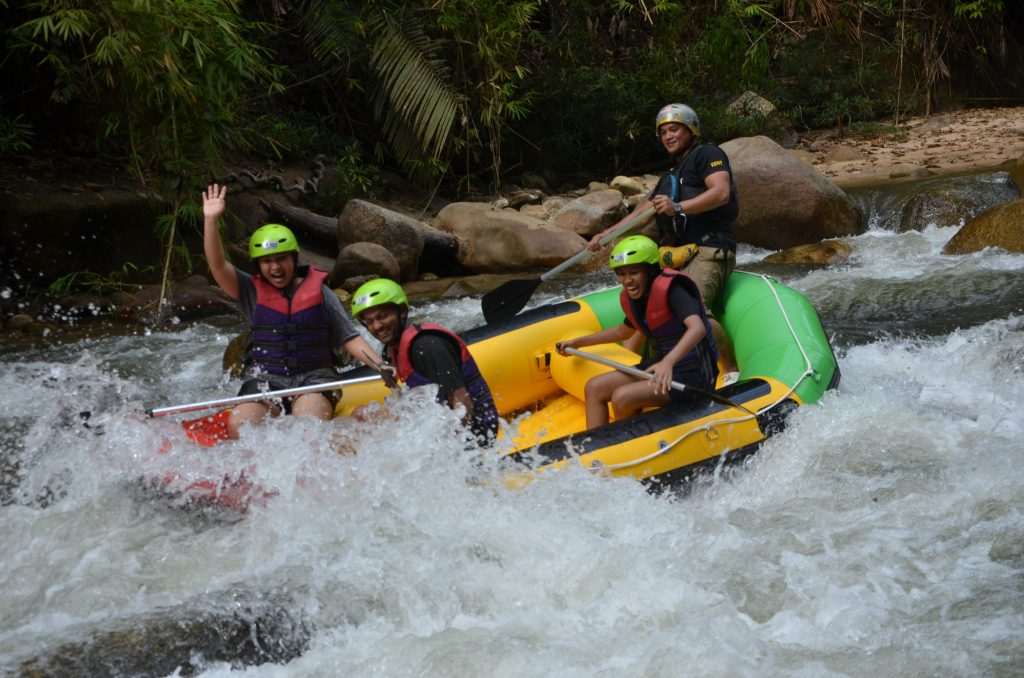 A lady with hands up mode in action with Ipoh Rafting